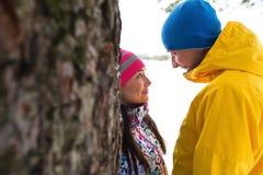 Pares jovenes en el bosque del invierno Foto de archivo libre de regalías