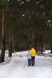Pares jovenes en el bosque del invierno Imagen de archivo libre de regalías