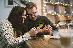 Pares jovenes en el café que se sienta con smartphone y café Imagenes de archivo