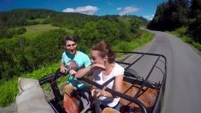 Pares jovenes en el camino en un jeep con un de tragante abierto en las montañas El individuo y la muchacha están viajando en una metrajes