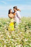 Pares jovenes en el campo asoleado de flores Fotografía de archivo