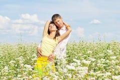 Pares jovenes en el campo de flores Fotografía de archivo