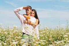 Pares jovenes en el campo de flores Imagen de archivo