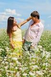 Pares jovenes en el campo de flores Foto de archivo