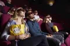 Pares jovenes en el cine que lleva los vidrios 3D que miran la película Fotos de archivo