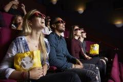 Pares jovenes en el cine que lleva los vidrios 3D que miran la película Foto de archivo