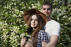 Pares jovenes en el jardín floreciente Fotos de archivo