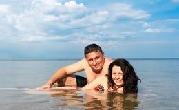 Pares jovenes en el mar Fotos de archivo