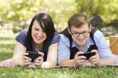 Pares jovenes en el parque que manda un SMS junto Fotos de archivo libres de regalías