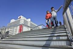 Pares jovenes en el puente peatonal, Pekín, China Foto de archivo libre de regalías