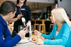 Pares jovenes en el restaurante que elige el vino Fotos de archivo