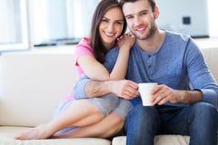 Pares jovenes en el sofá imagen de archivo libre de regalías