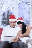 Pares jovenes en el sombrero de santa usando la tableta Fotos de archivo libres de regalías