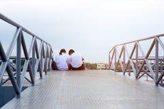 Pares jovenes en el uniforme escolar que se sienta en un puente Foto de archivo