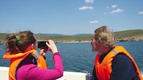 Pares jovenes en el viaje del chaleco salvavidas en un paseo del barco abajo del lago La muchacha toma la imagen con el teléfono  metrajes