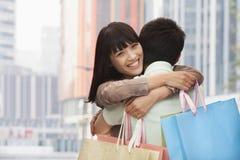 Pares jovenes en hacer compras que va del amor y el abarcamiento con los bolsos de compras coloridos en la calle, Pekín, China Imagen de archivo libre de regalías