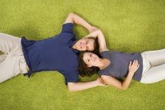 Pares jovenes en la alfombra verde Fotografía de archivo