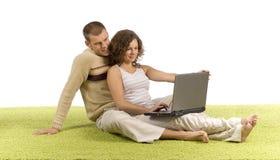 Pares jovenes en la alfombra verde con la computadora portátil fotos de archivo