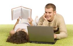 Pares jovenes en la alfombra verde con la computadora portátil y el libro Fotografía de archivo libre de regalías