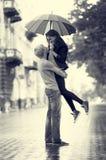 Pares jovenes en la calle de la ciudad con el paraguas Foto de archivo libre de regalías