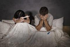 Pares jovenes en la cama asustada y subrayada después de resultado positivo en prueba de embarazo con la mujer embarazada que cue imagenes de archivo