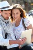 Pares jovenes en la ciudad que visita y que usa la tableta Imagen de archivo