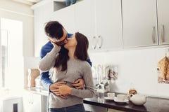 Pares jovenes en la cocina que abraza y que se besa imagenes de archivo