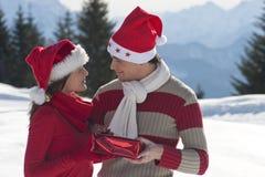 Pares jovenes en la nieve Fotografía de archivo libre de regalías