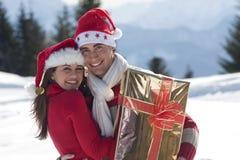Pares jovenes en la nieve Imagen de archivo libre de regalías