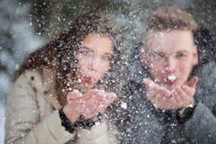 Pares jovenes en la nieve que sopla del amor ausente Fotografía de archivo libre de regalías