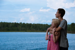 Pares jovenes en la orilla del lago Fotos de archivo libres de regalías