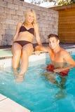 Pares jovenes en la piscina imagenes de archivo