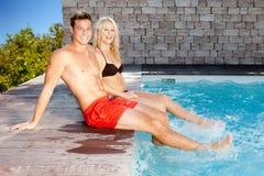 Pares jovenes en la piscina imagen de archivo