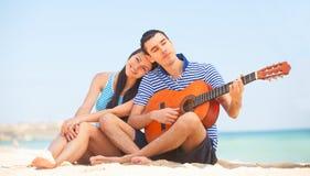 Pares jovenes en la playa Imágenes de archivo libres de regalías
