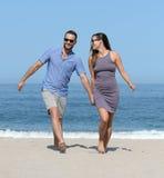 Pares jovenes en la playa arenosa Imagen de archivo