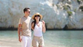 Pares jovenes en la playa blanca en las vacaciones de verano almacen de metraje de vídeo