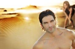 Pares jovenes en la playa con el foco en hombre Fotografía de archivo