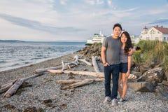 Pares jovenes en la playa con el transbordador y el faro Foto de archivo libre de regalías