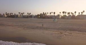 Pares jovenes en la playa de Los Ángeles en la salida del sol almacen de metraje de vídeo