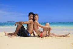 Pares jovenes en la playa en Hawaii Imagen de archivo libre de regalías