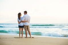 Pares jovenes en la playa en la puesta del sol Imagen de archivo libre de regalías