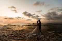 Pares jovenes en la playa en la puesta del sol fotografía de archivo