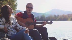 Pares jovenes en la playa que juega la canción del canto de la guitarra en un día de verano al lado del río de la montaña Fotografía de archivo