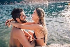 Pares jovenes en la playa que se divierte imagenes de archivo