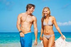Pares jovenes en la playa tropical Foto de archivo libre de regalías