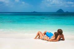 Pares jovenes en la playa tropical Imagen de archivo libre de regalías