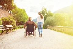 Pares jovenes en la silla de ruedas que da un paseo en el parque imagenes de archivo