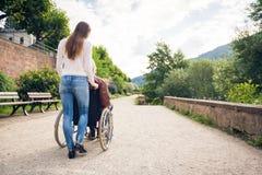 Pares jovenes en la silla de ruedas que da un paseo en el parque fotografía de archivo