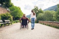 Pares jovenes en la silla de ruedas que da un paseo en el parque fotografía de archivo libre de regalías