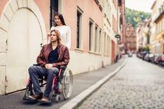 Pares jovenes en la silla de ruedas que da un paseo en la ciudad Imagen de archivo